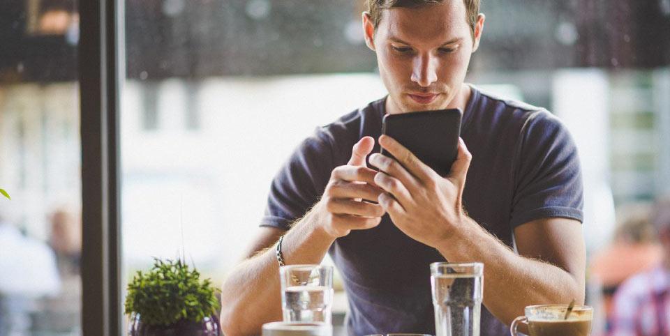Mann schaut in sein Handy