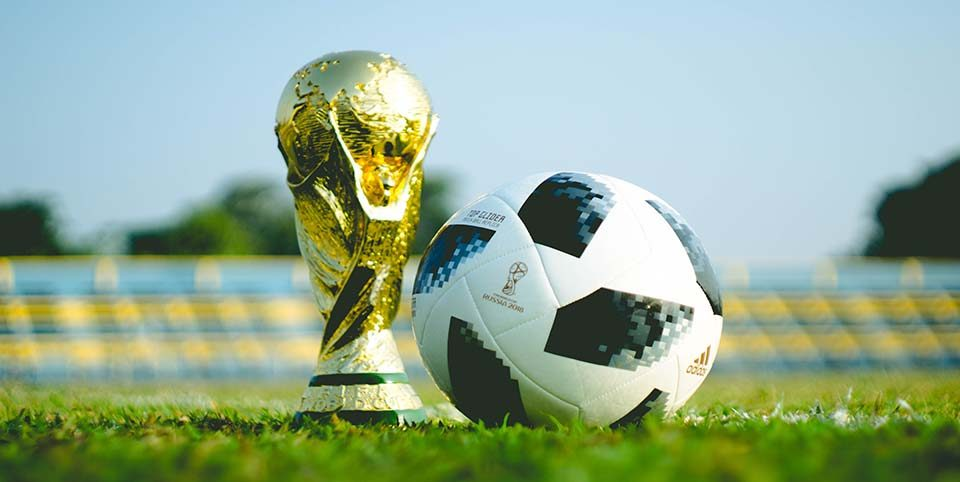 Fußball auf einem Fußballfeld vor der WM-Trophäe