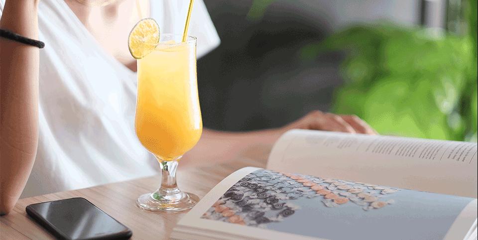 Cocktail, Handy und Zeitung auf einem Tisch