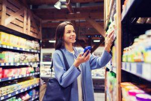 Frau mit Handy beim Einkaufen