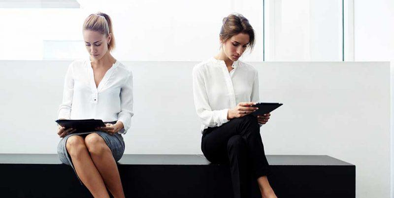 Zwei Frauen sitzen in einem Wartezimmer an Tablets