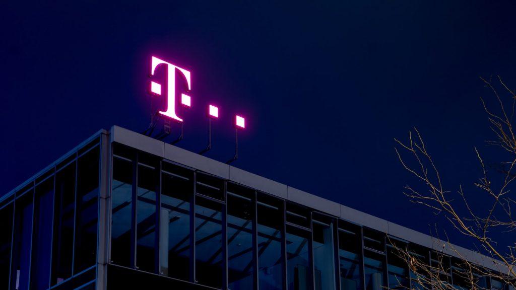 Das Telekom Logo leuchtet nachts auf einem Bürogebäude