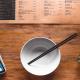 Menü, Schüssel und Smartphone auf einem Holztisch