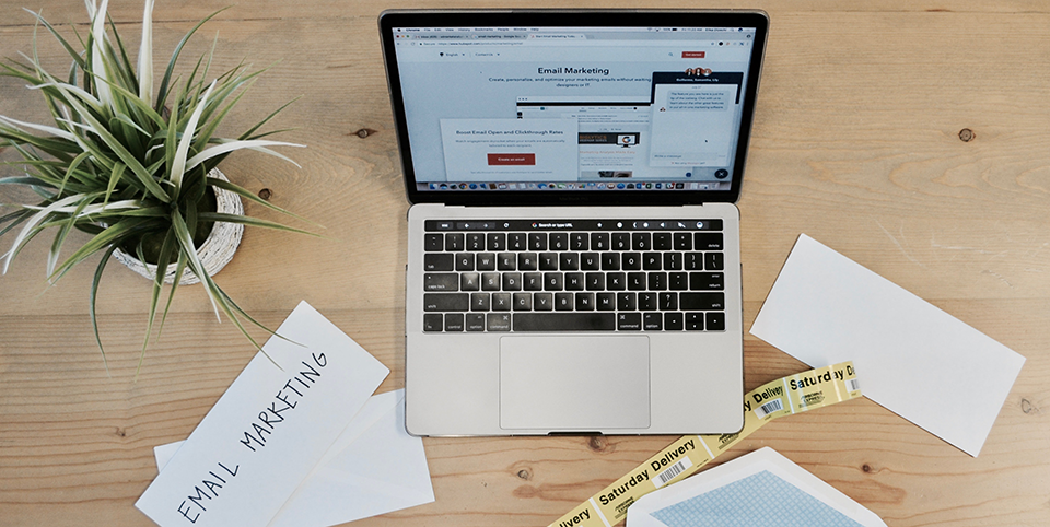 Laptop und Unterlagen auf einem Holztisch
