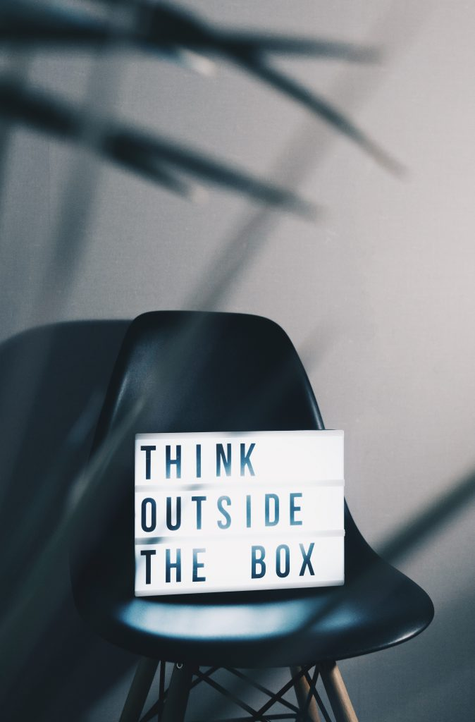 """schwarzer Stuhl mit Schild mit Aufschrift """"think outside the box"""""""