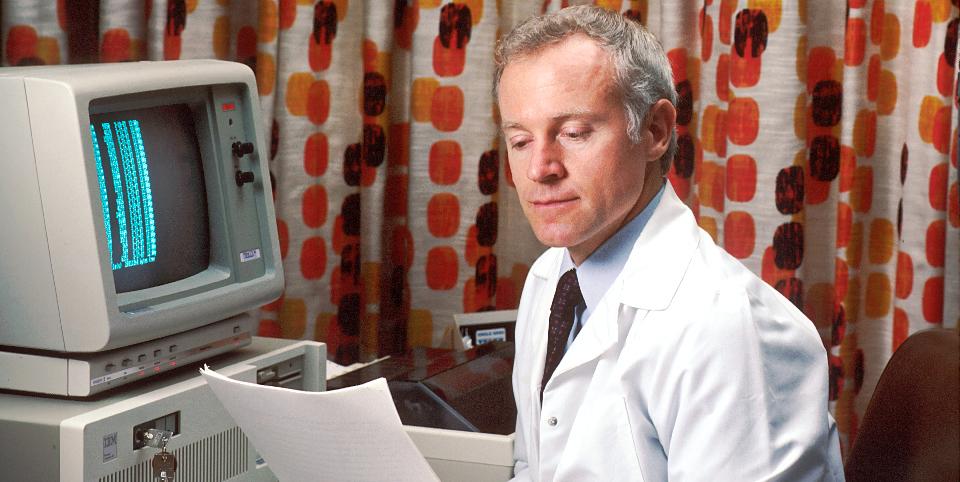 Arzt der vor einem sehr alten Computer sitzt