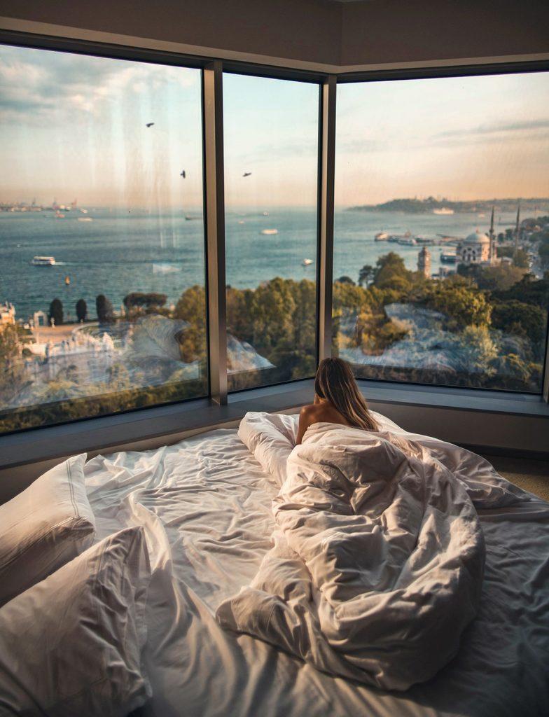 Frau in Hotelzimmer mit Ausblick