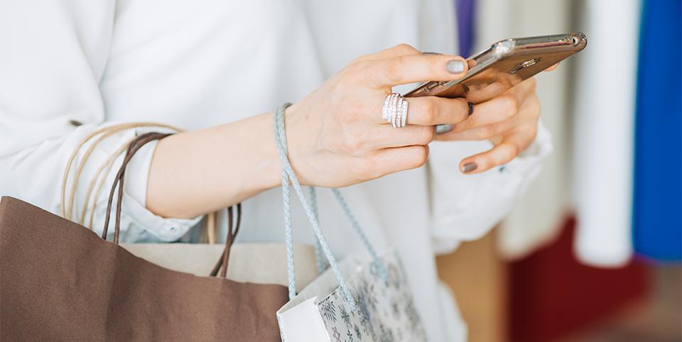 Frau nutzt Smartphone in einem Geschäft