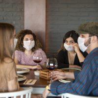 Freunde beim Essen mit Maske