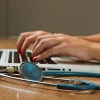 Person mit Stethoskop an einem Laptop